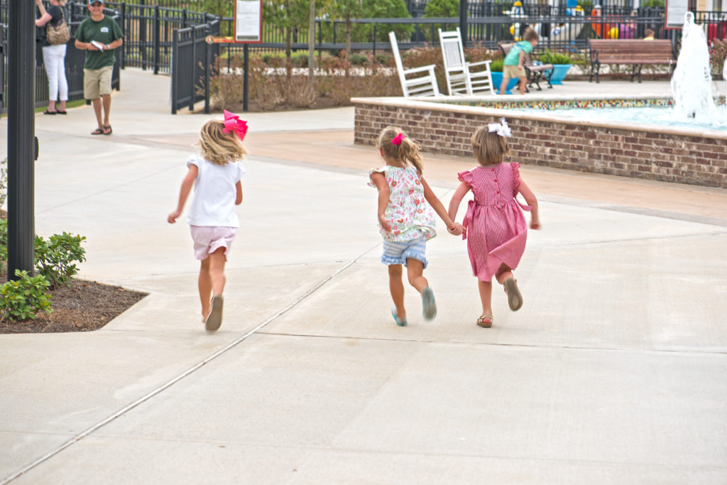 Three small children running through The Park at OWA