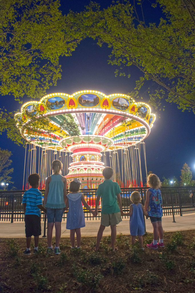 Children watching the Flying Carousel at night