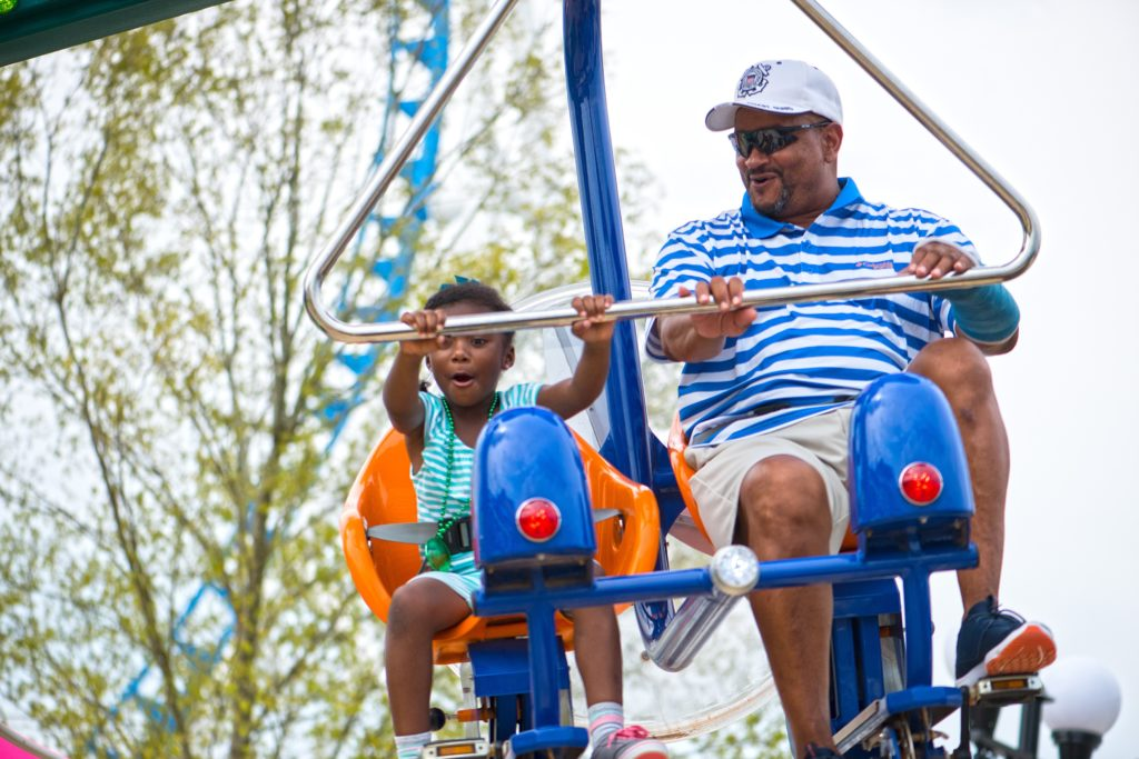 A family swinging through the air on the Flutter By ride