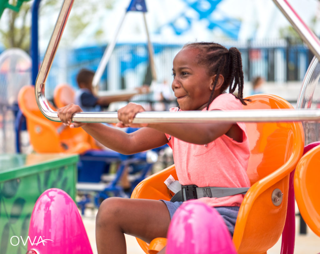 A young girl smiling while riding the Flutter By ride