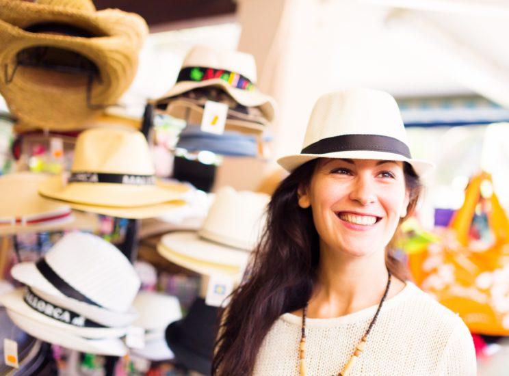 A tourist shopping for a sunhat