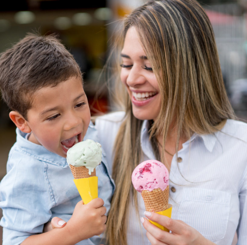 A woman and child enjoying ice cream cones