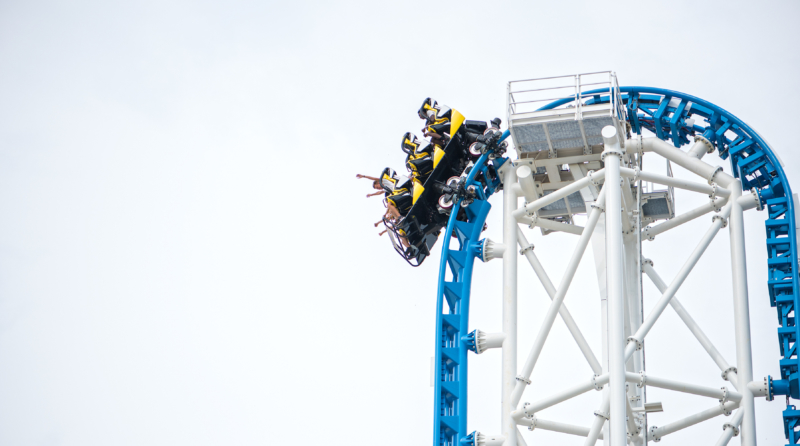 Riders at the top of a roller coaster
