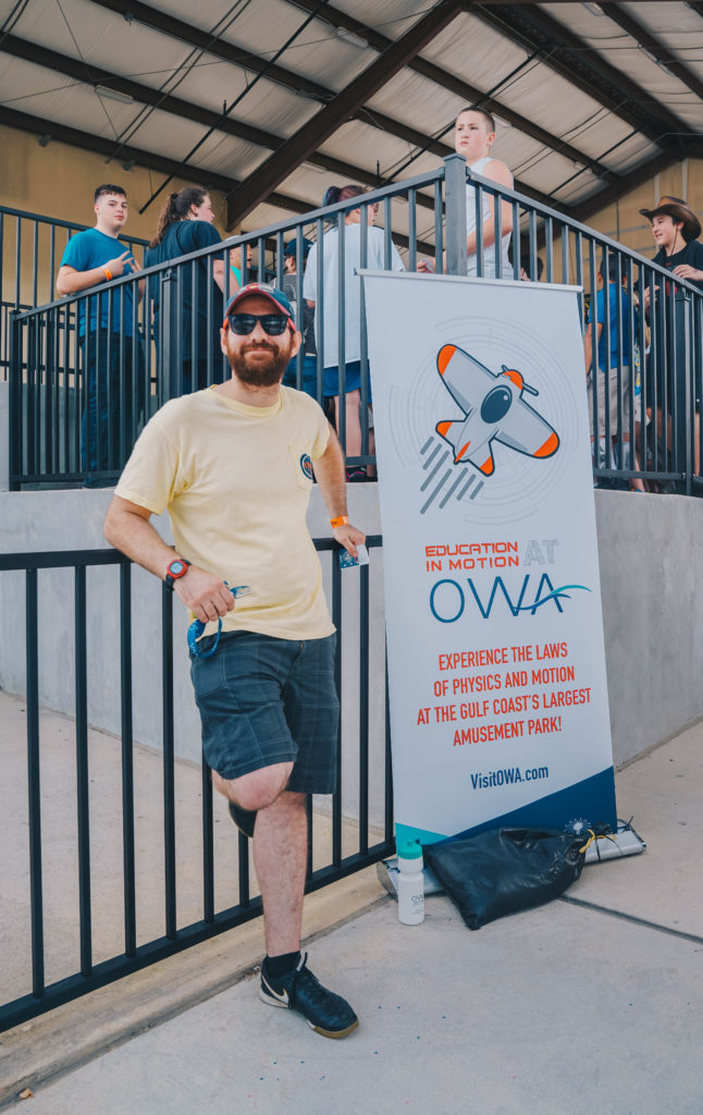 A man leaning against a railing beside an Education in Motion banner