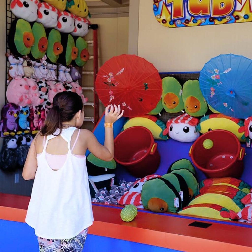 A child playing a Midway Game