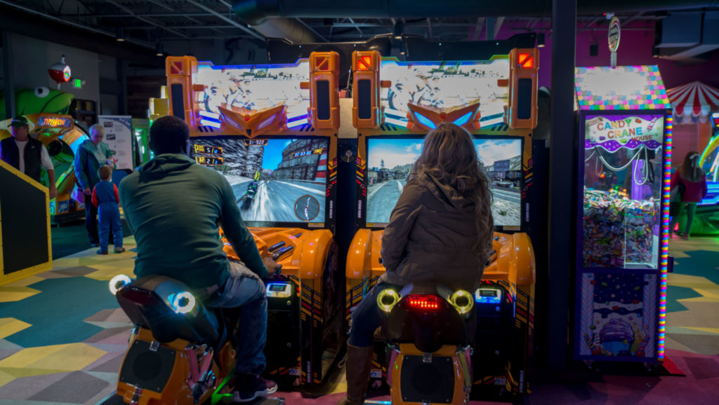 Two people playing a motorcycle arcade game