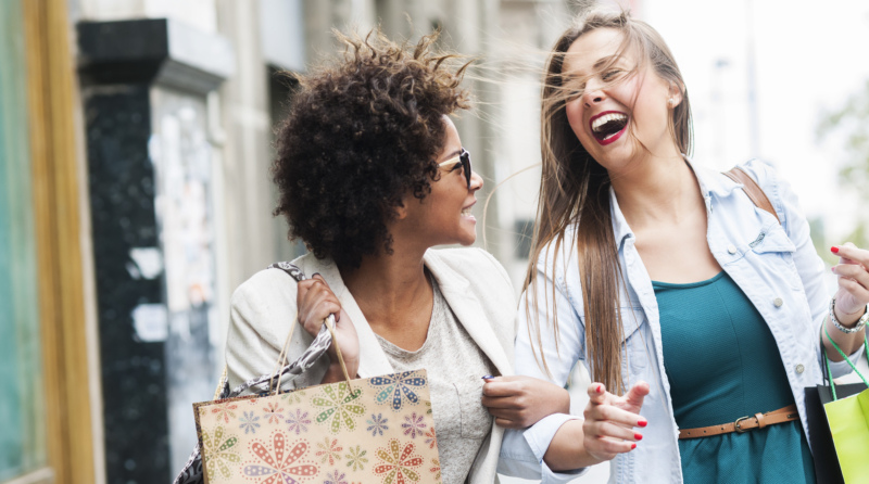 Two laughing women carrying shopping bags
