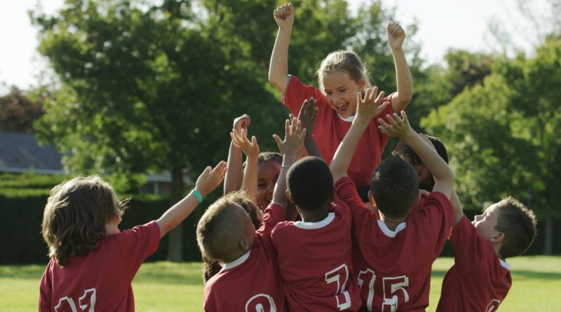 Kids soccer team cheering their teammate