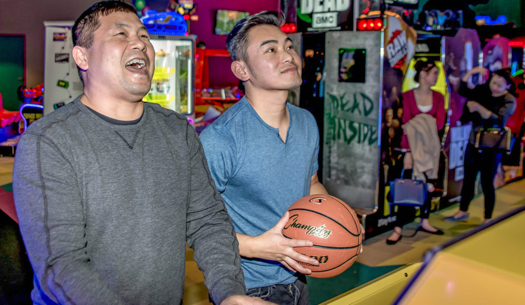 Two men playing a basketball arcade game