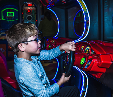 A child playing a racing arcade game