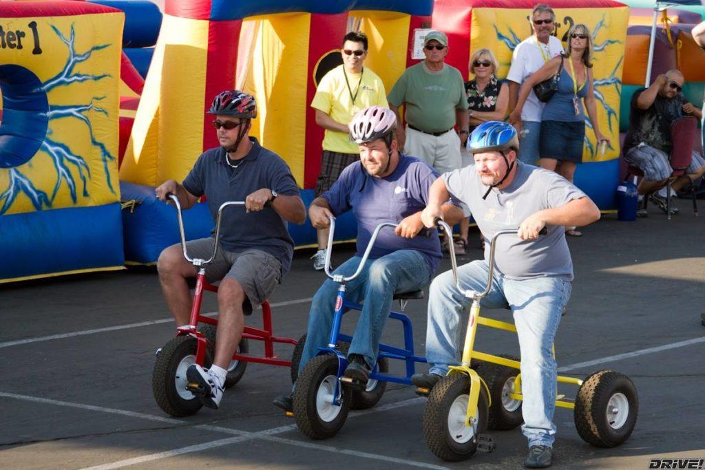 Three men riding tricycles
