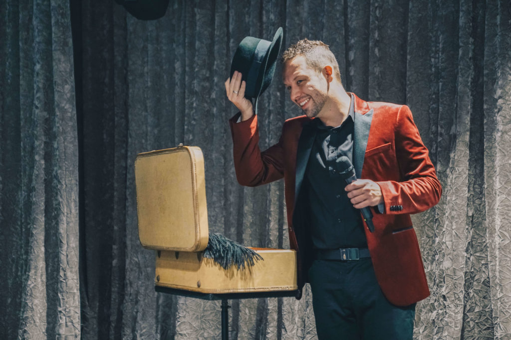 Brandon Styles standing beside a suitcase and tipping his hat