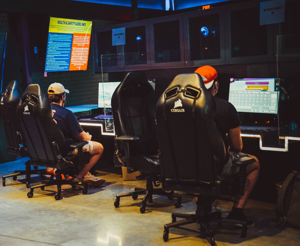 Two people seated in gaming chairs in the Clash eSports Center