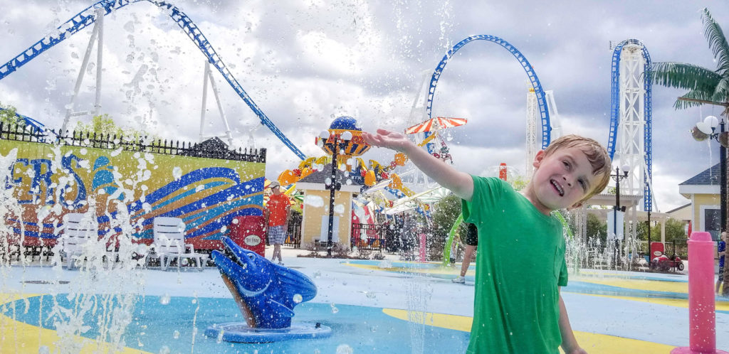 A child waving from the Wacky Waters splash pad