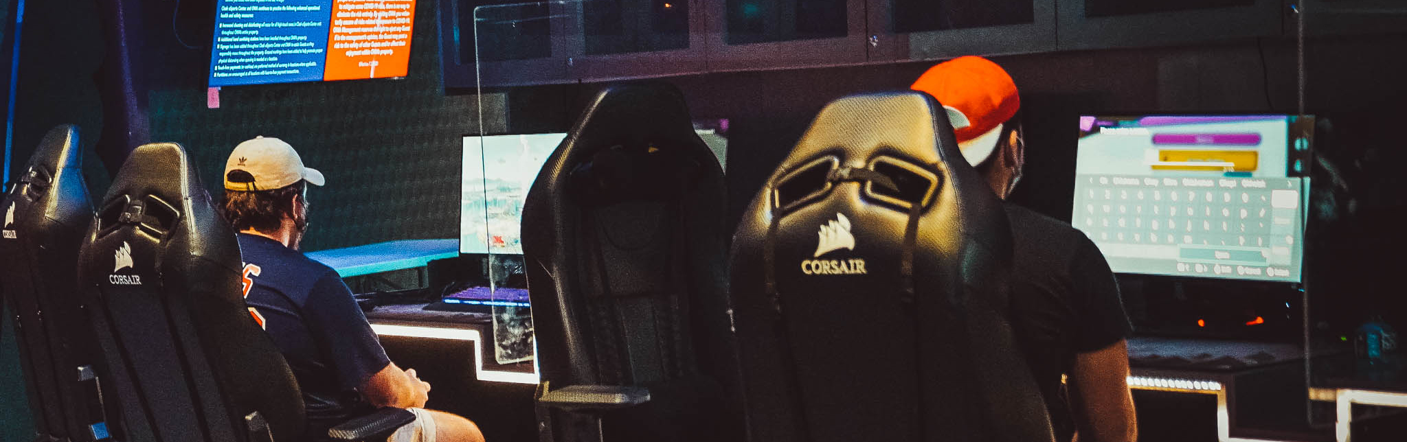 Two people seated in gaming chairs at Clash eSports Center